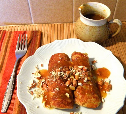 Rolled up Pancakes with persimmon sauce, extra sauce in cruet