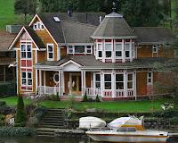 Fachada de casa de lago con un yate