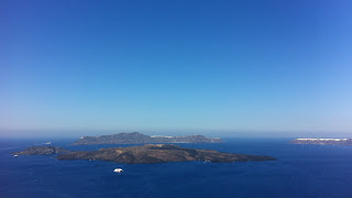The view of volcano tip out in the center of the caldera from the surrounding cliffs of Santorini.