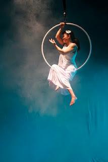 Estrela - Ceci Yeda, atriz e bailarina cadeirante, dança sorridente e suspensa numa lira, sob luz delicada e fundo azul.