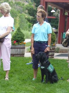 A Southwest Brighteyes puppy raiser poses with her black Lab puppy.
