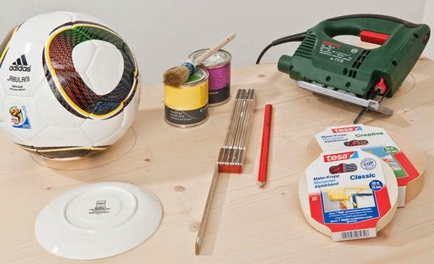 مواد العمل: منشار، قلم الرصاص، صحن الفنجان، كرات القدم، شريط لاصق، صباغة، لوح خشبي