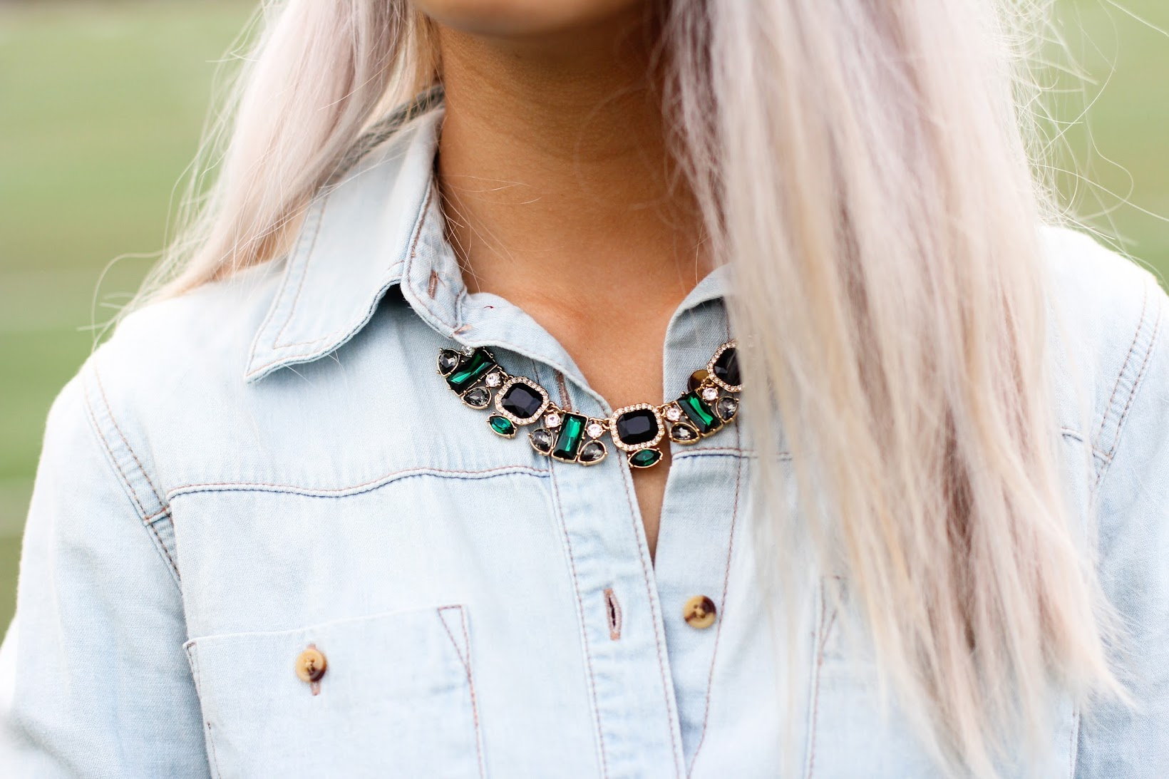 A green J.Crew statement necklace tucked under the collar.