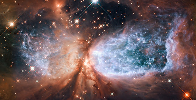 This image from the NASA/ESA Hubble Space Telescope shows Sh 2-106, or S106 for short. This is a compact star forming region in the constellation Cygnus (The Swan). A newly-formed star called S106 IR is shrouded in dust at the center of the image, and is responsible for the surrounding gas cloud's hourglass-like shape and the turbulence visible within. Light from glowing hydrogen is colored blue in this image. Credit: NASA/ESA