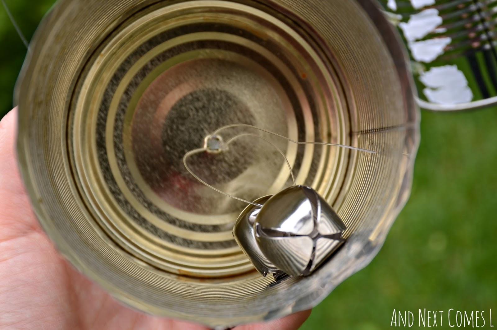 Jingle bells in a tin can on a DIY recycled outdoor music station from And Next Comes L