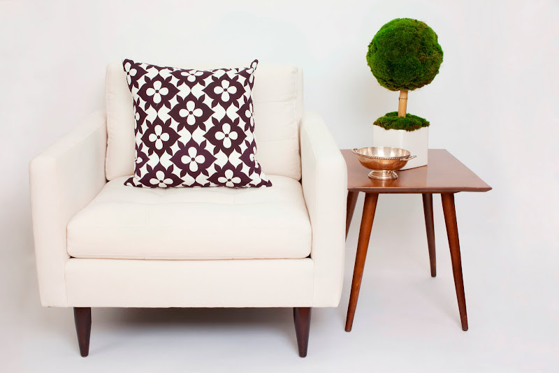 Nbaynadamas Cotton Collection pillow in Coco's Flower on a white armchair next to a wood side table with a small topiary