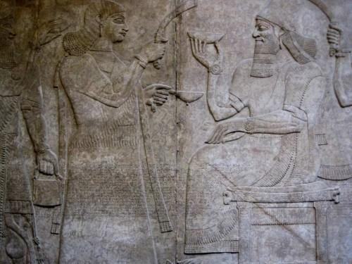 """Nimrud (antigua Kalhu), el norte de Irak Neo-asirio, 883 a 859 aC  El Rey entronizado entre los asistentes  Estos panel puede haber venido de un salón de banquetes en el palacio del rey Asurnasirpal II (883-859 aC). El relieve tallado es particularmente fino, con muy delicadas incisiones en la ropa que indican bordado. Grandes áreas de la superficie serían originalmente se han destacado en la pintura, los rastros de los cuales sobreviven con las sandalias. A diferencia de muchos de los relieves del palacio de Assurnasirpal, esta serie de paneles no se dividió en registros distintos. No obstante, la inscripción del estándar """", que se repite en muchos de los monumentos de Assurnasirpal, se inscribe en el centro. Registra su títulos, ascendencia y logros.  Un rey asirio casi siempre es identificable por su corona: un fez con una tapa de punta, rodeado de una diadema con dos tiras, posiblemente, de tela, que cuelgan por detrás y por la espalda.  Detrás del rey un asistente tiene un matamoscas y las armas del rey. Puesto que él es imberbe la cifra puede ser identificado ya sea como un joven o, posiblemente, un eunuco. Los eunucos se mencionan en los textos antiguos y fueron empleados a menudo en la corte. Al estar castrados fueron incapaces de formar una familia para rivalizar con la del rey. Los asistentes suelen ser representados con la cabeza descubierta como en este caso, a pesar de que se muestran a veces con bandas para la cabeza."""