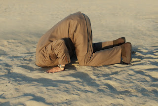 Businessman with head in sand