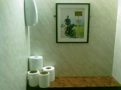 steve mcqueen from the great escape on his motorbike hanging in a picture from a lavatory somewhere in Bucharest hiding with toilet paper