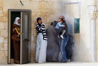 À Palestine: une famille essaye de se protéger de la police israélienne qui vient de lancer des lacrymogènes suite à des jets de pierres et bombes.