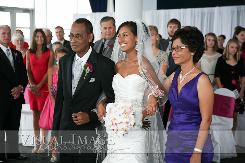 Bride walking down aisle with father and mother in the Pilot House at Discovery World