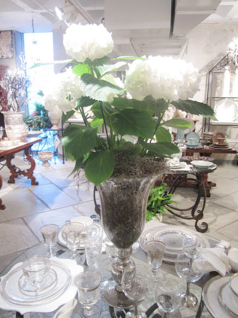 Close up of table setting and large white hydrangea plant in a glass vase on the round glass table above