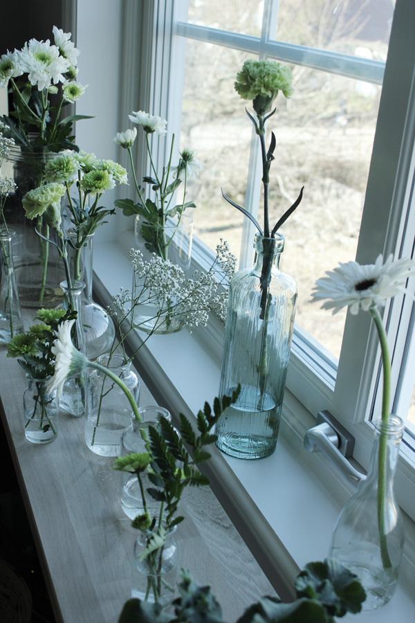 glasflaskor i fönstret med blommor