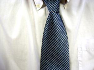 Gambar busana kerja pria dengan kemeja putih dan dasi kotak-kotak