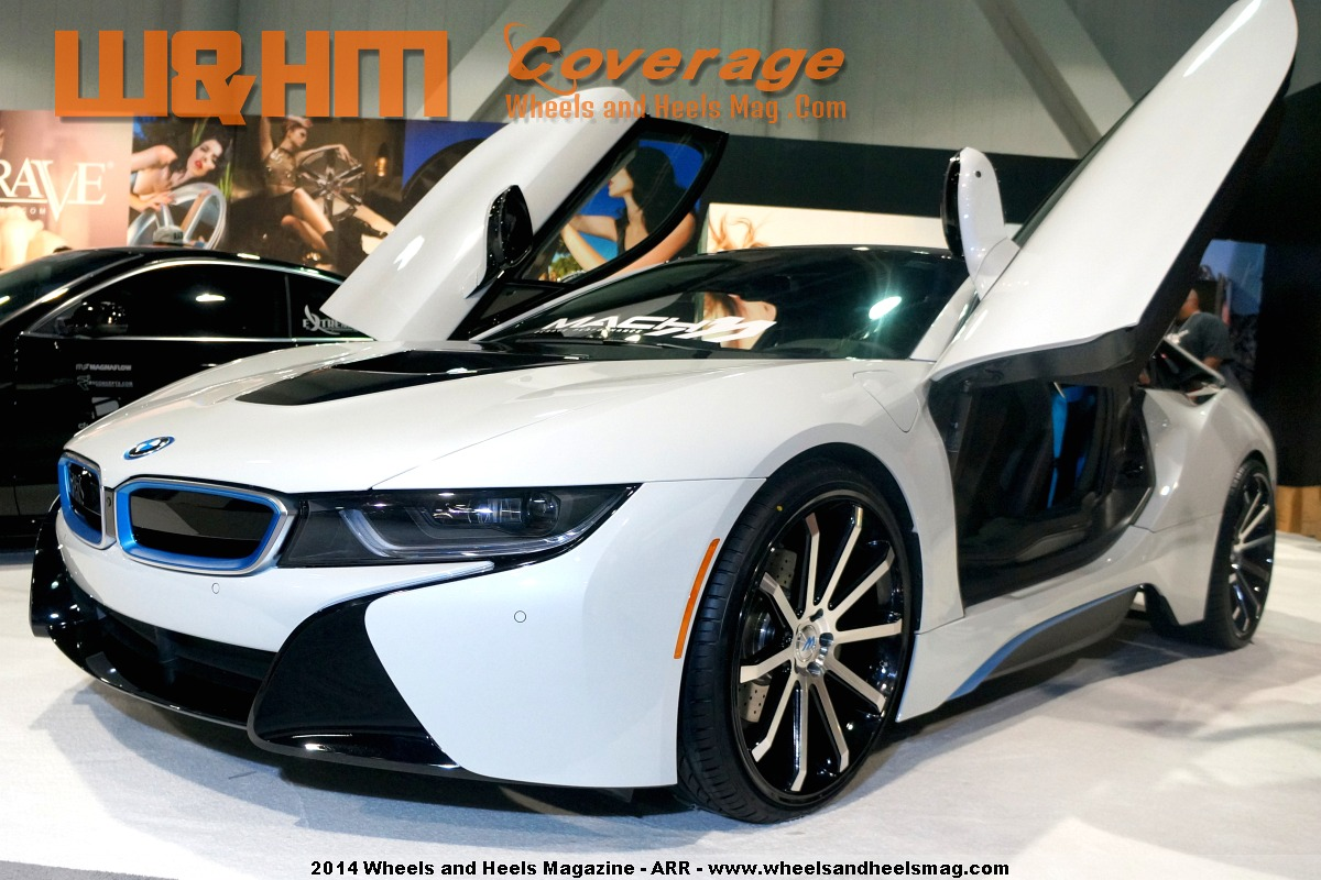 A white 2015 BMW i8 in 2Crave booth with both doors spring up on display