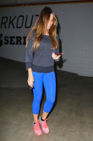Sofia Vergara wearing blue spandex and holding her mobile phone