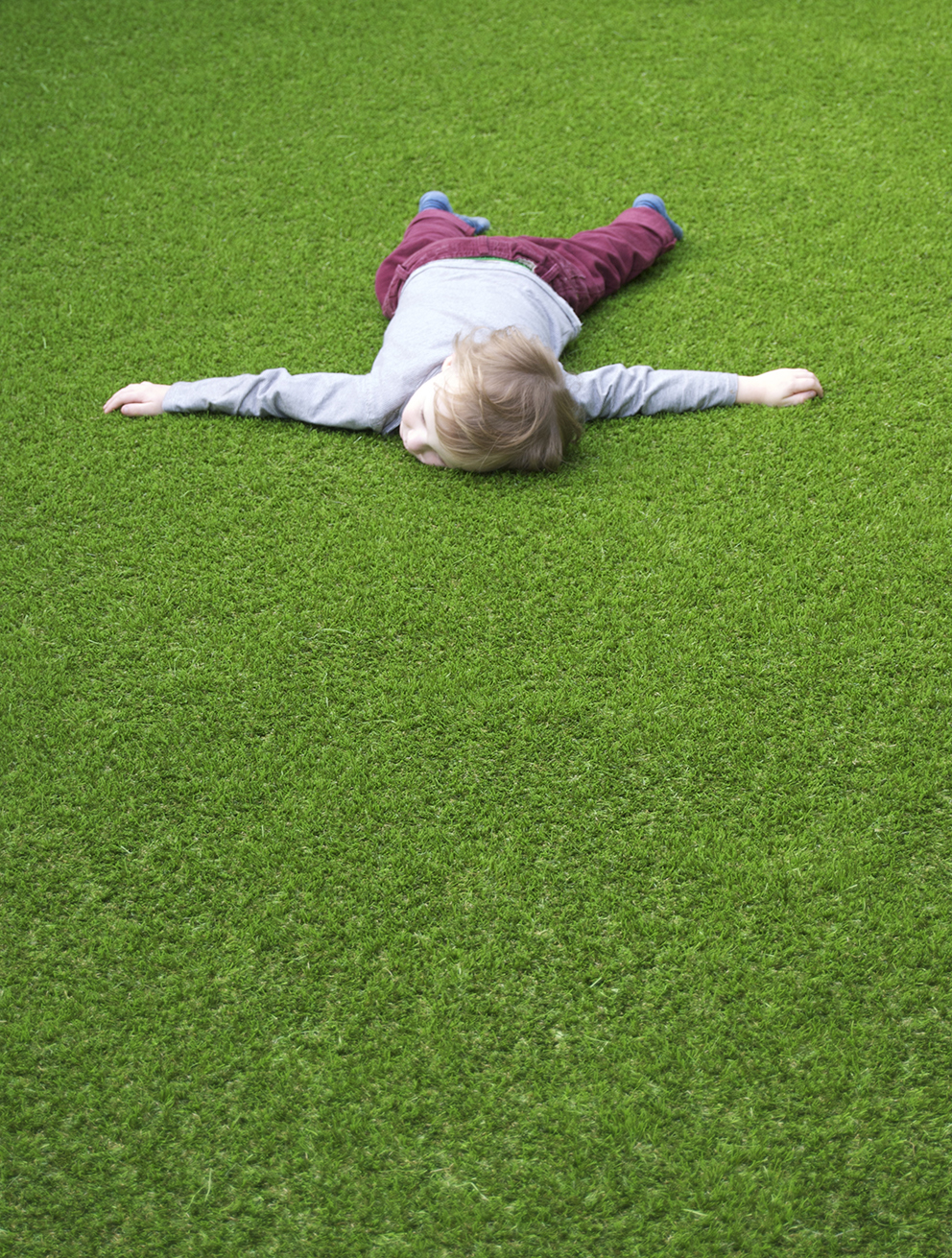 Boy lying on artificial lawn - French For Pineapple Blog