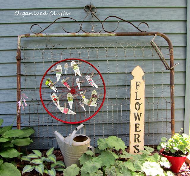 Old rusty gate, bike wheel plant tag organizer