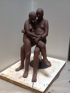 clay of two nude figures, the female sitting in the male's lap