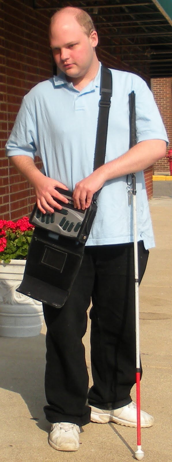 Photo of Scott Davert, standing on the sidewalk with his white cane and assistive technology