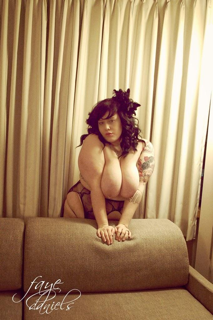Faye Daniels debout derriere un fauteuil nue en collant ajouré