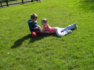 boy and girl wrestling for ownership of football