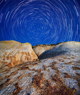 long exposure of rocks with circle of stars behind