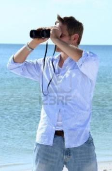 man-on-beach-with-binoculars-in-his-hand - Beach Body Language