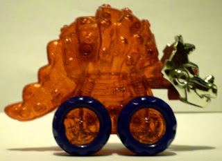 Side view of unknown red dinosaur toy with wheels and chrome head