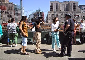 A press crew interviewing a police officer.