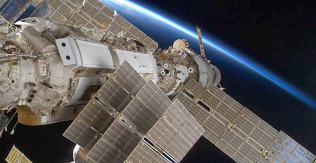 Zarya module in the foreground with solar arrays folded, Zvezda behind it. Credit: NASA