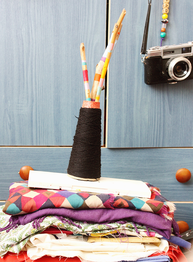 painted sticks in wool spool, on pile of fabric with yashica camera in background