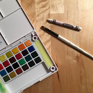 White crayon, black and white paintbrush next to a colorful watercolor set