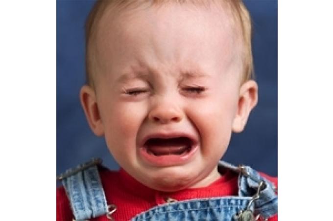 طفل يغلق عينيه ويبكي بصورة خلفية زرقاء وبردائه الملون
