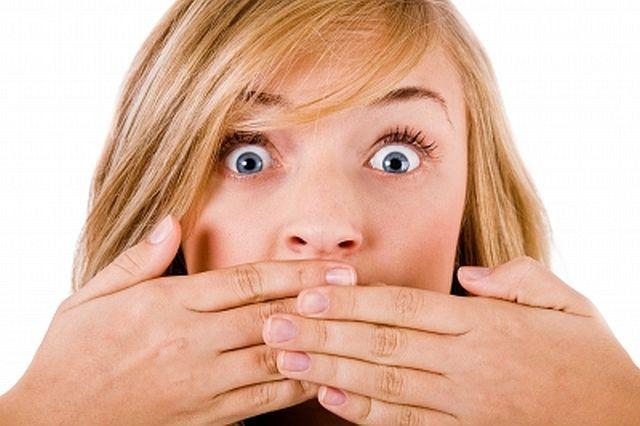 mulher tampando a boca com as mãos