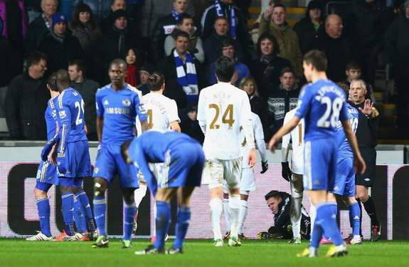 A ballboy lays on the ground after being kicked by Chelsea player Eden Hazard