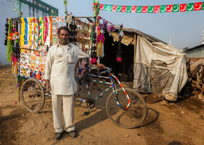 A Meer Communty Male in front of his House with items he makes with livelihood help from VSSM