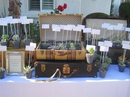 poner nombres de mesas en una maleta antigua en boda de inspiración vintage y romántica
