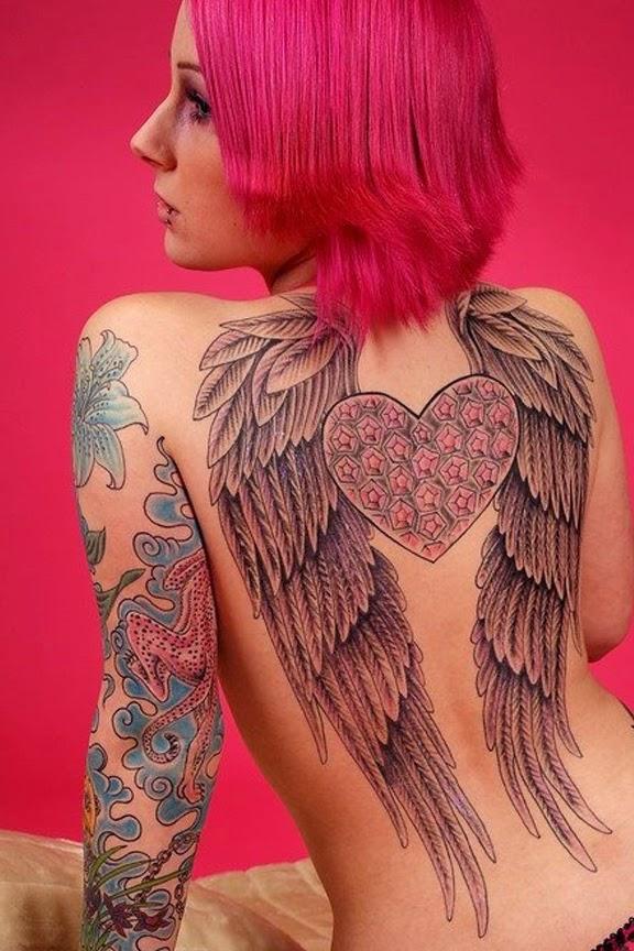 chicade espaldas con el pelo rosa, vemos tatuaje de dos alas que ocupan su espalda