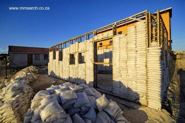 Casa de bolsas de arena en construcción