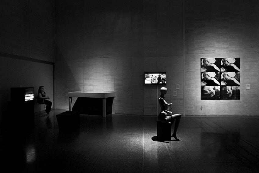 Pormenor de uma sala de exposição com uma apresentação em vídeo à esquerda, ao centro uma estatueta em madeira, num banco e ao fundo na parede, um conjunto de quadros à direita, outra apresentação vídeo em frente e um móvel à esquerda. Ambiente muito soturno, com luzes muito fortes a emergirem da escuridão. Ao canto, uma vigilante do museu, sentada numa cadeira
