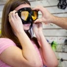 girl tries on a mask for scuba diving made from tempered glass