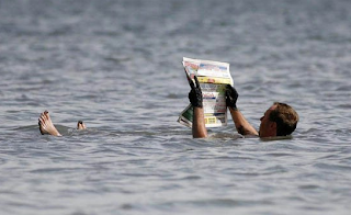 funny picture: Man reading newspaper in the water