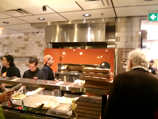 behind the counter at blaze pizza showing the stainless steel fire oven