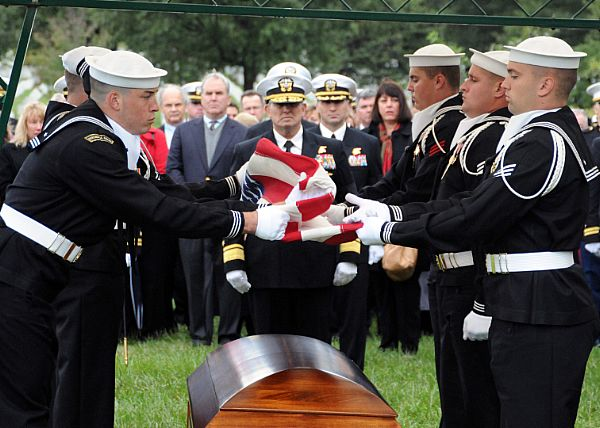 Members of the U.S. Navy Honor Guard fold an American flag over the ...