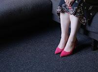 Rote Pumps und Fingernägel auf der Couch elegant