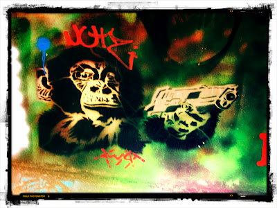 Graffiti showing chimp holding pistol