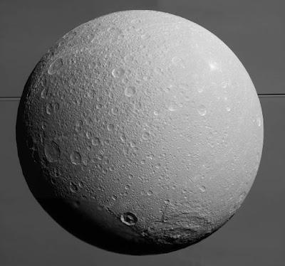 Диона на фоне Сатурна и его колец