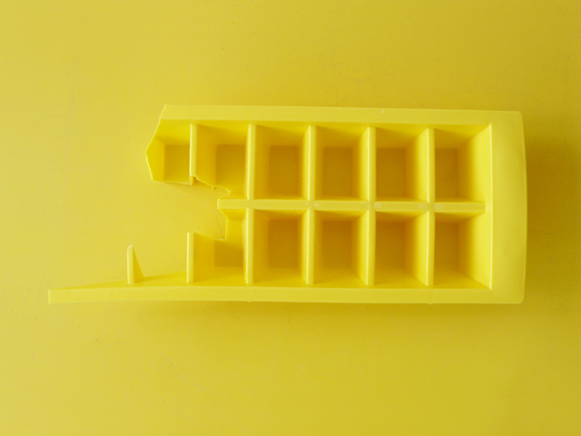 Most of an yellow ice tray.
