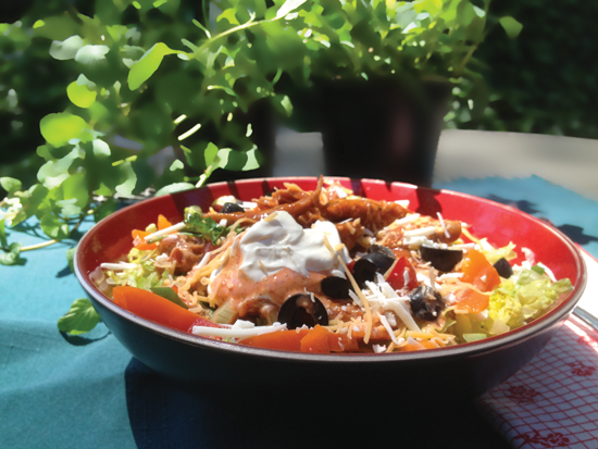 Image of fresh enchilada salad topped with creamy enchilada dressing and a dollop of sour cream.